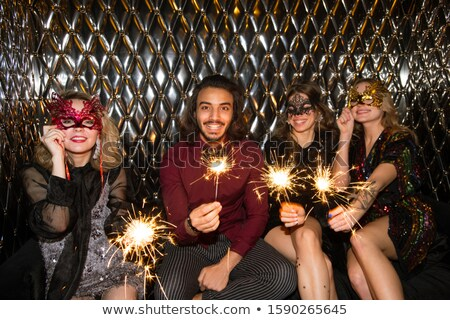 Three happy girls in venetian masks and guy holding sparkling bengal lights Stock photo © pressmaster
