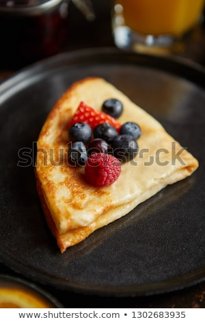 Tasety homemade pancake on black ceramic plate. Stock photo © dash