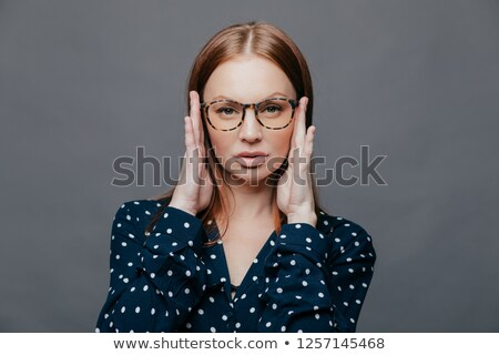 Headshot of serious female teacher keeps hands on head, has self confident facial expression, wears  Stock photo © vkstudio