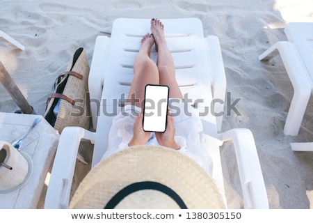 Woman laying on the beach with mobile telephone Stock photo © photography33