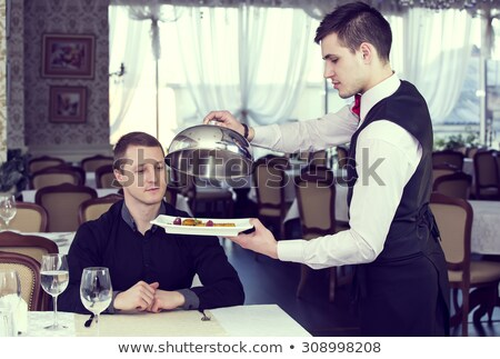 Young waiter serving an older customer Stock photo © photography33