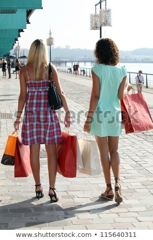 two young women holding carton bags and walking on a wharf Stock photo © photography33