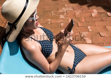 Woman tanning in a lounge chair Stock photo © cwzahner