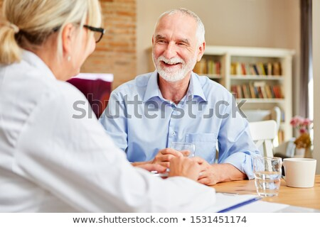 nurse chatting with senior man during home visit stock photo © highwaystarz