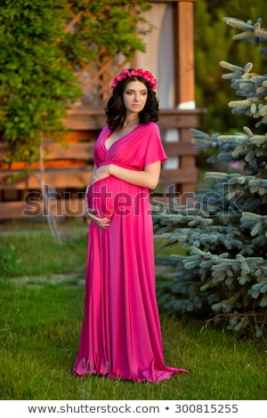 Beautiful pregnant woman with chaplet of flowers wearing in pink Stock photo © Victoria_Andreas