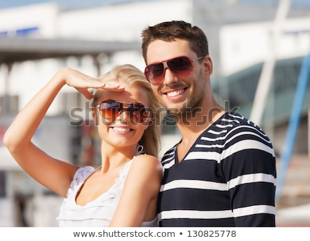 Beautiful happy couple standing on a yacht Stock photo © deandrobot