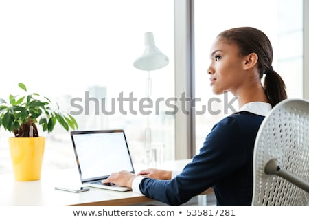 woman in black dress sitting on chair and looking away stock photo © deandrobot