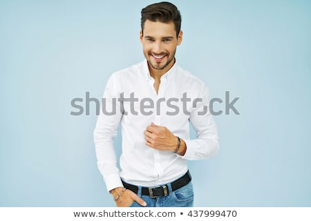 attractive young man in casual shirt and jeans posing stock photo © feedough