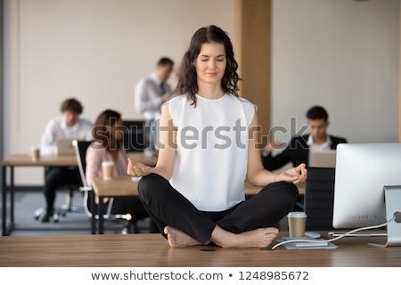 Peaceful businesswoman meditating in lotus pose. Stock photo © RAStudio