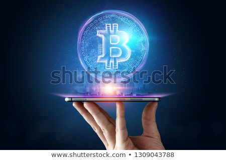 hand with smartphone and bitcoin hologram Stock photo © dolgachov