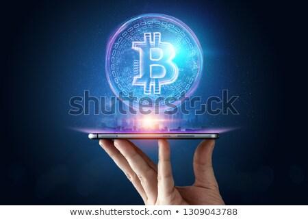 hand with smartphone and bitcoin hologram stock photo © dolgachov