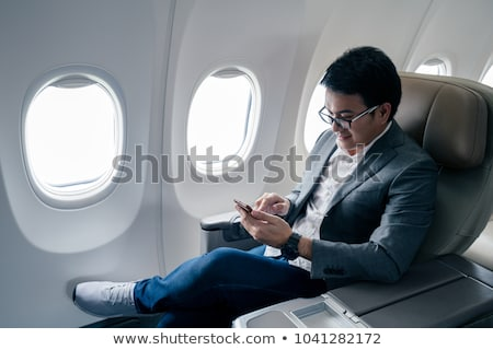 happy man sitting in plane with smartphone Stock photo © dolgachov
