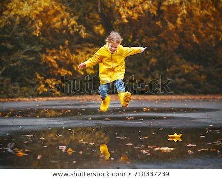Gyerek piros esőkabát ugrik lány gyermek Stock fotó © colematt