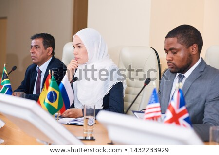 Pensive young female delegate in hijab listening to one of colleagues Stock photo © pressmaster