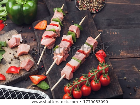 raw pork kebab with paprika on chopping board with fresh vegetables and disposable charcoal grill on stock photo © denismart