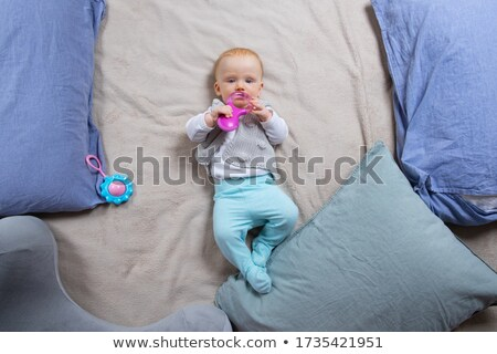 Baby Lying on Back and Plays with Rattle Isolated Stock photo © robuart