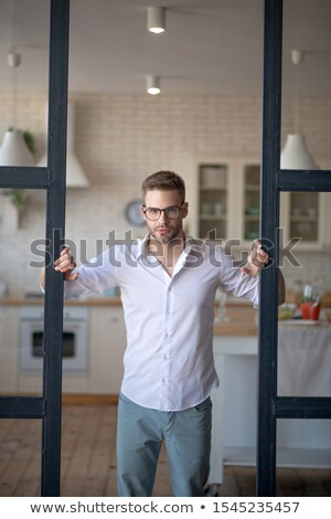 Millennial man opening shirt in blue room Stock photo © wavebreak_media