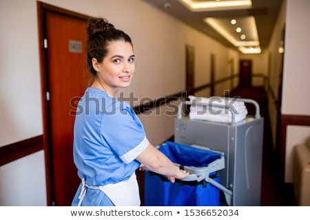 Young brunette chamber maid in uniform looking at you while pushing cart Stock photo © pressmaster
