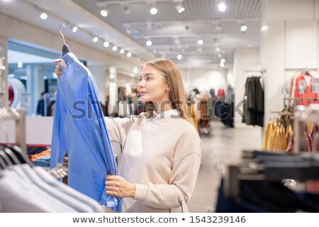 Casual blonde woman looking at blue shirt in clothing department Stock photo © pressmaster