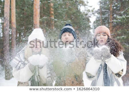 Group of young friends in winterwear blowing snow off their hands in park Stock photo © pressmaster