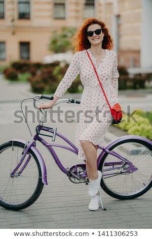 Pleased female has ride bike, dressed in fashionable outfit, smiles happily, stands near bicycle, be Stock photo © vkstudio