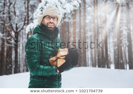 Unshaven smiling male holds pile of firewood, going to make fire to warm himself in frosty weather,  Stock photo © vkstudio