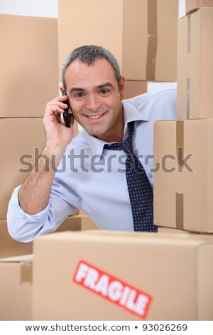 Stock photo: a 40-45 years old employee calling someone in a room full of cardboard boxes