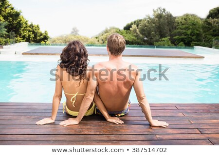 Portrait of a young couple sitting at the poolside Stock photo © photography33
