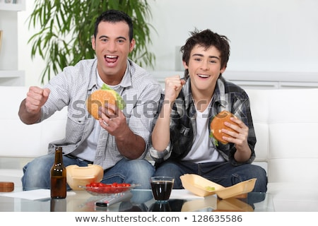 Father and son eating burgers in front of TV stock photo © photography33