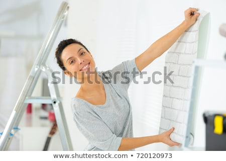 Young woman unrolling wallpaper Stock photo © photography33
