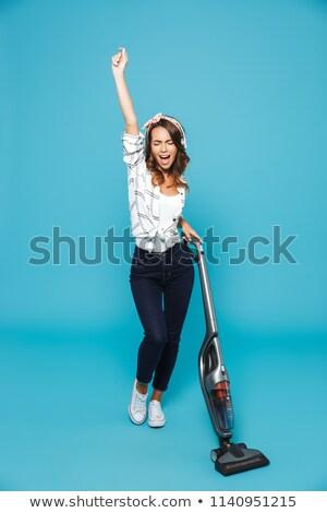 Woman listening music over headphones while vacuuming stock photo © wavebreak_media