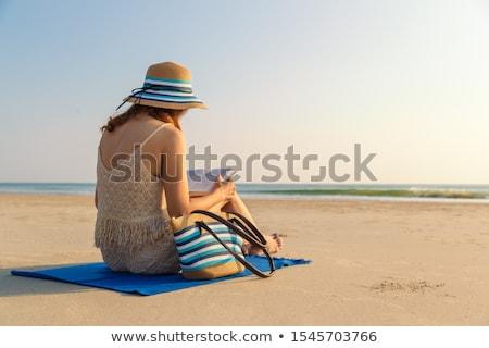 ストックフォト: 女性 · 座って · ビーチ · 帽子