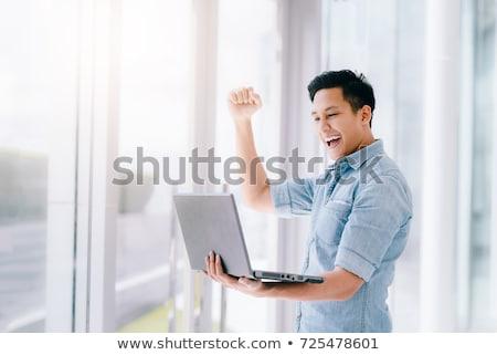 Iş adamı silah dizüstü bilgisayar mutlu zafer yalıtılmış Stok fotoğraf © doupix