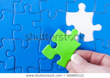 Woman's hand placing missing piece in Jigsaw puzzle  signifying  Stock photo © jenbray