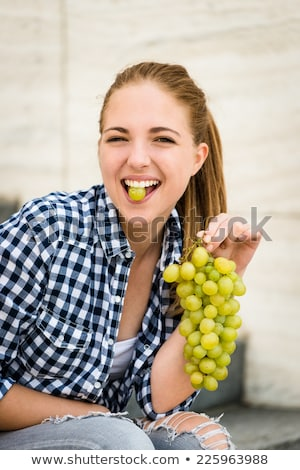 Young woman about to bite into a bunch of grapes Stock photo © dash