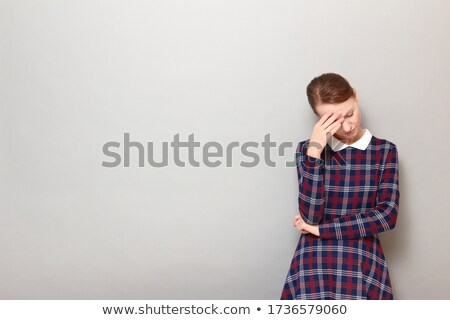 Portrait of young depressed woman looking down over gray background Stock photo © deandrobot
