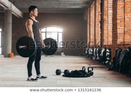 Mid section of a shirtless muscular man lifting barbell Stock photo © wavebreak_media