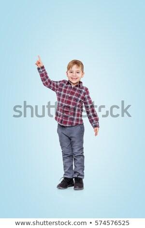 Surpreendido pequeno menino indicação para cima branco Foto stock © wavebreak_media