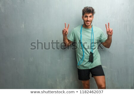 Confident fitness man holding skipping rope  Stock photo © deandrobot