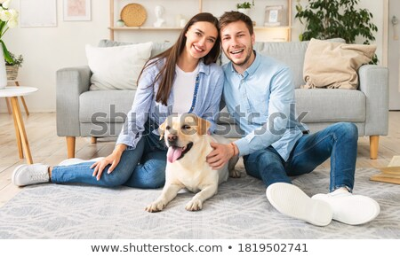 cute family petting their golden retriever on the couch stock photo © wavebreak_media