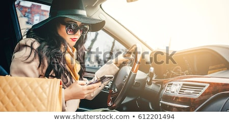fashion beautiful girl using her mobile phone in the car stock photo © nenetus