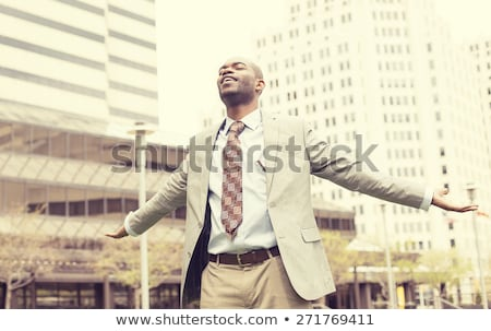 Young handsome business man celebrates freedom success arms raised Stock photo © ichiosea