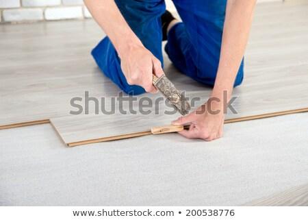 Carpenter measuring wood piece for flooring Stock photo © Kzenon