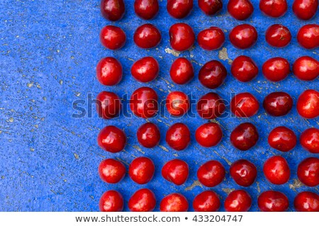 Square arrangement of ripe cherries on blue textrured background Stock photo © szabiphotography