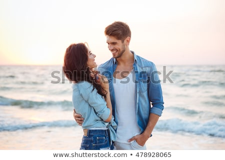 happy young couple standing at the beach and hugging stock photo © deandrobot