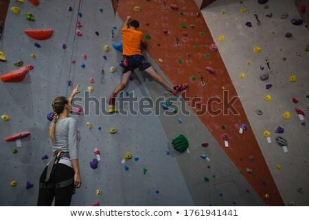 Vrouw rotsklimmen fitness studio vastbesloten muur Stockfoto © wavebreak_media