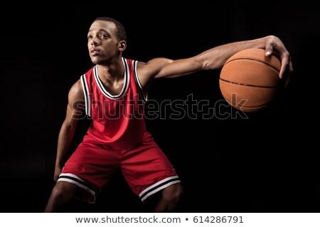 african sporty man in sports uniform playing basketball on black Stock photo © LightFieldStudios