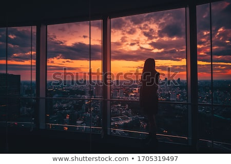 Stock photo: Sunset sky with beautiful girl rear view