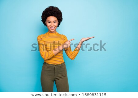 Cheerful young lady in yellow shirt holding copyspace in hand. Stock photo © deandrobot