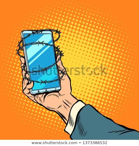 Phone barbed wire in hand Stock photo © studiostoks